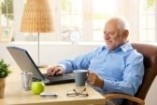 8748721-smiling-senior-man-using-laptop-typing-on-keyboard-holding-coffee-mug-at-home
